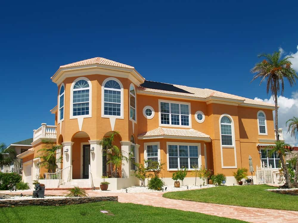 Large luxury house with orange exterior and white trims.