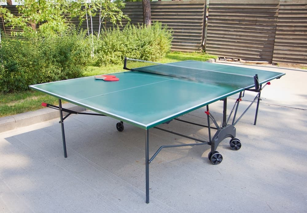 Green outdoor ping-pong table with wheels standing on concrete flooring outdoors with wood private fence and green plants nearby.