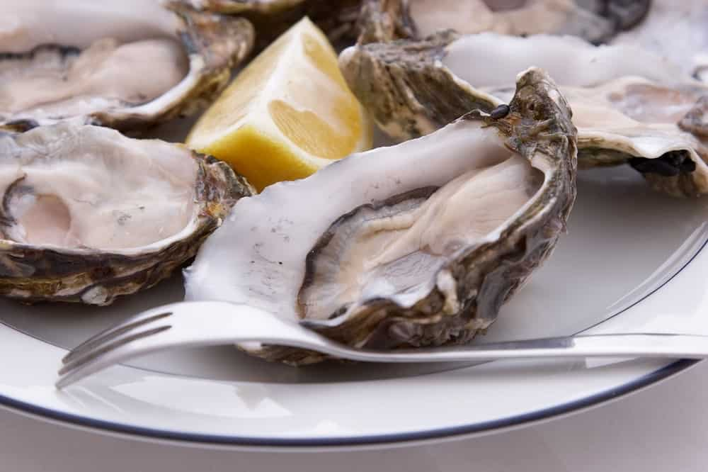Oyster fork on a plate of oysters and a slice of lemon.