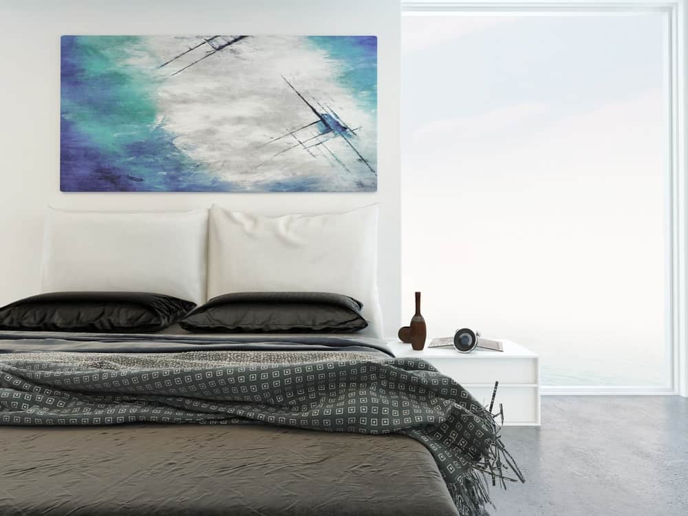 White bedroom with panorama windows and an abstract painting above the bed.