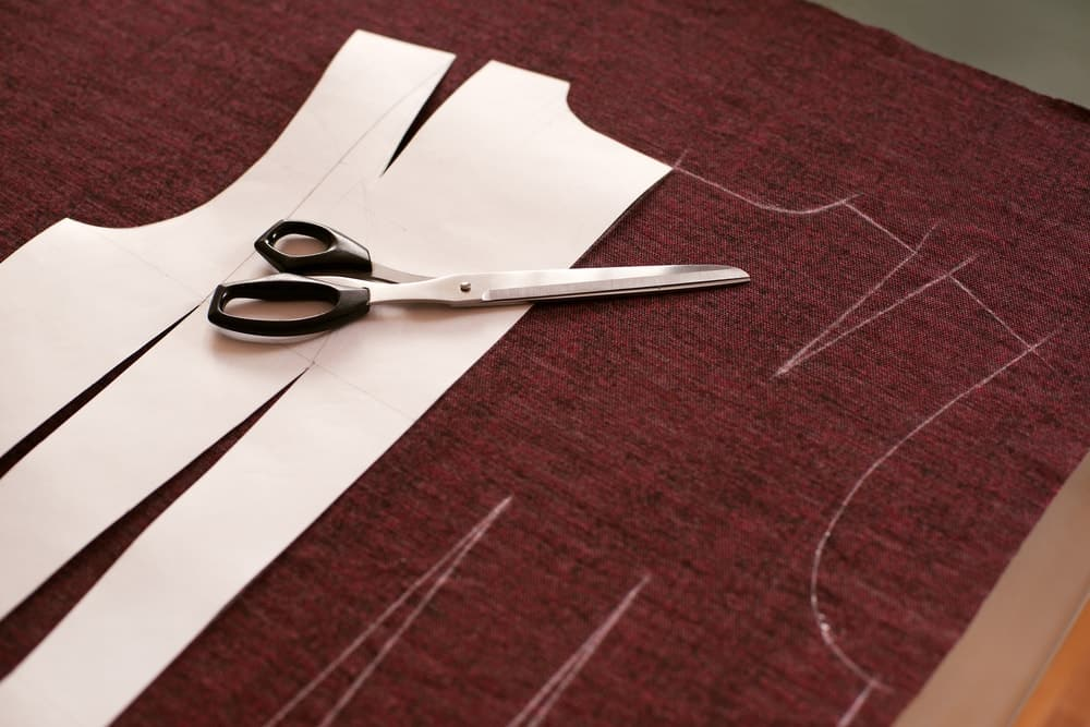 Scissors are being used to cut out patterns from paper.