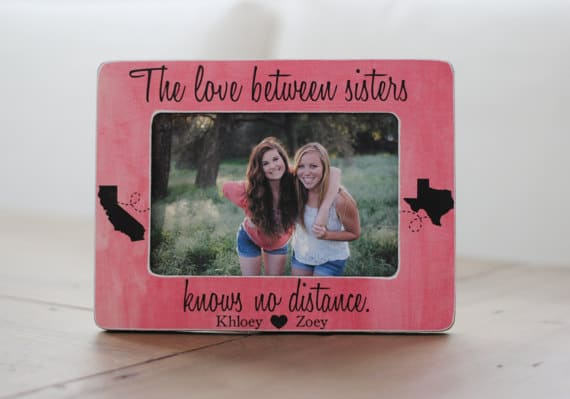 Pink, wooden picture frame personalized for two sisters.