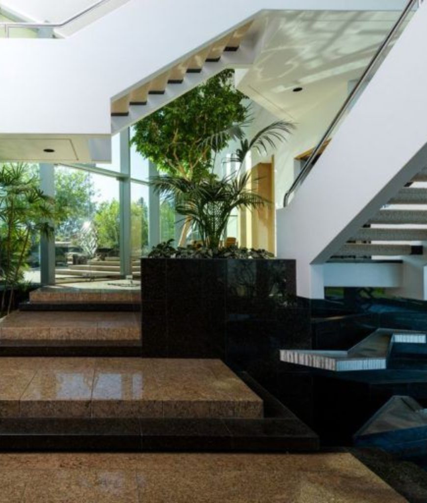 The house's indoor features a beautiful set of staircases along with stunning flooring and beautiful plants.