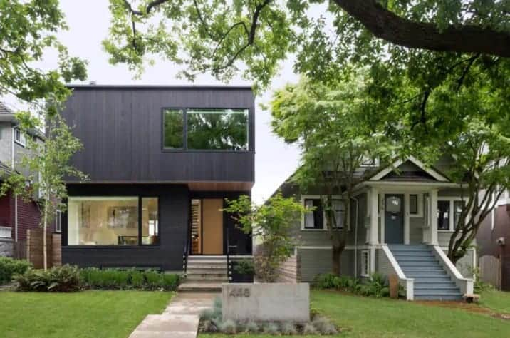 A black house with glass windows. It features a small front yard garden with a well-maintained lawn area.