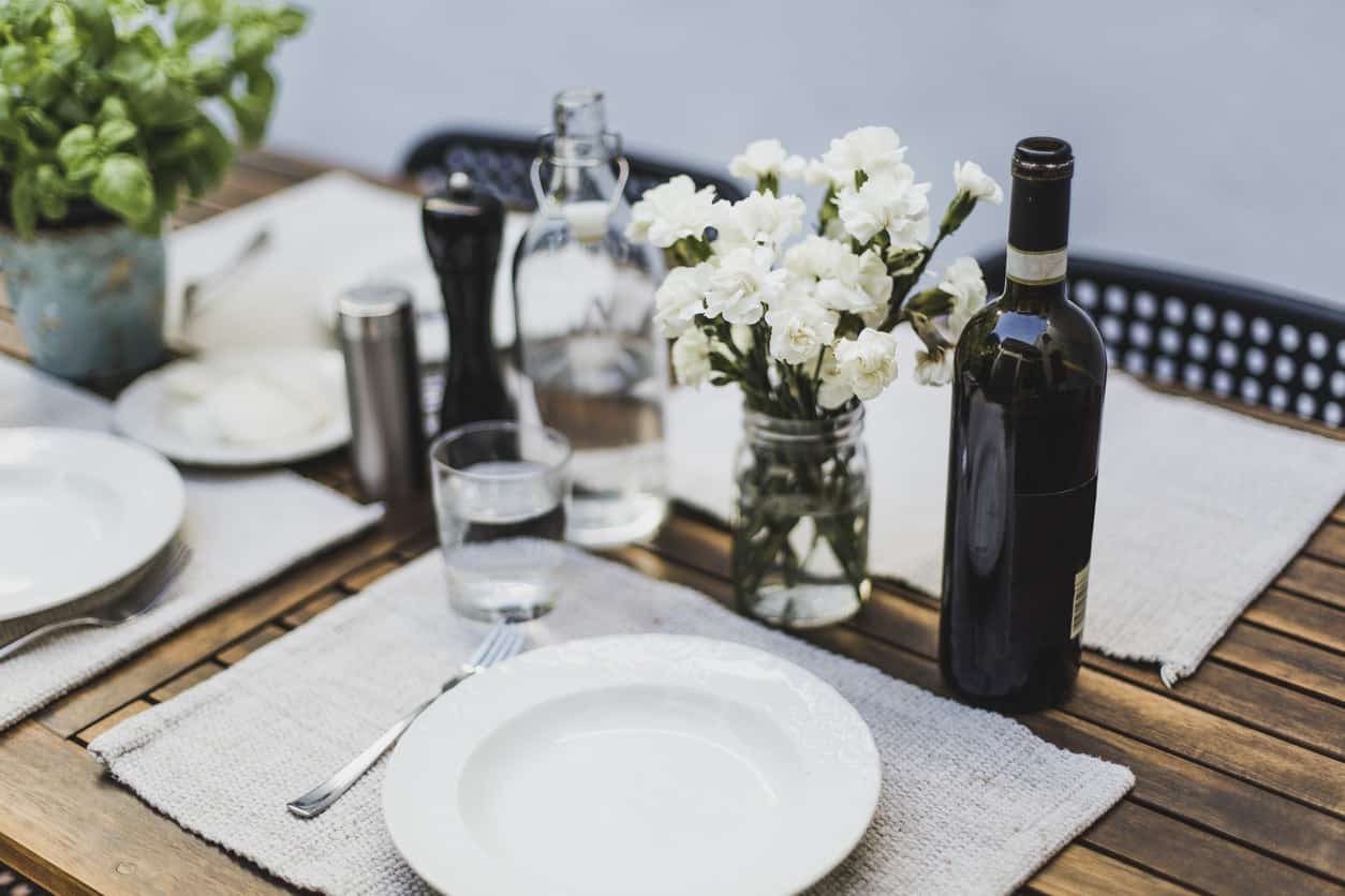 Bare table setting with cloth placements under ceramic plates, stainless steel utensils, and glass on wooden dining table.
