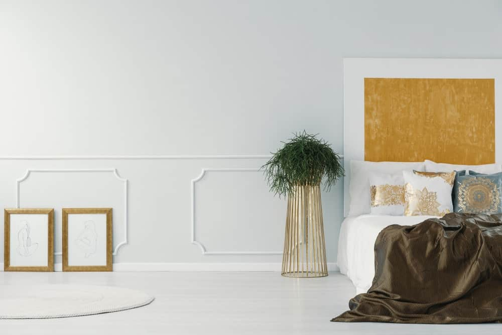 White modern bedroom with indoor plant on golden plant stand as nightstand alternative.