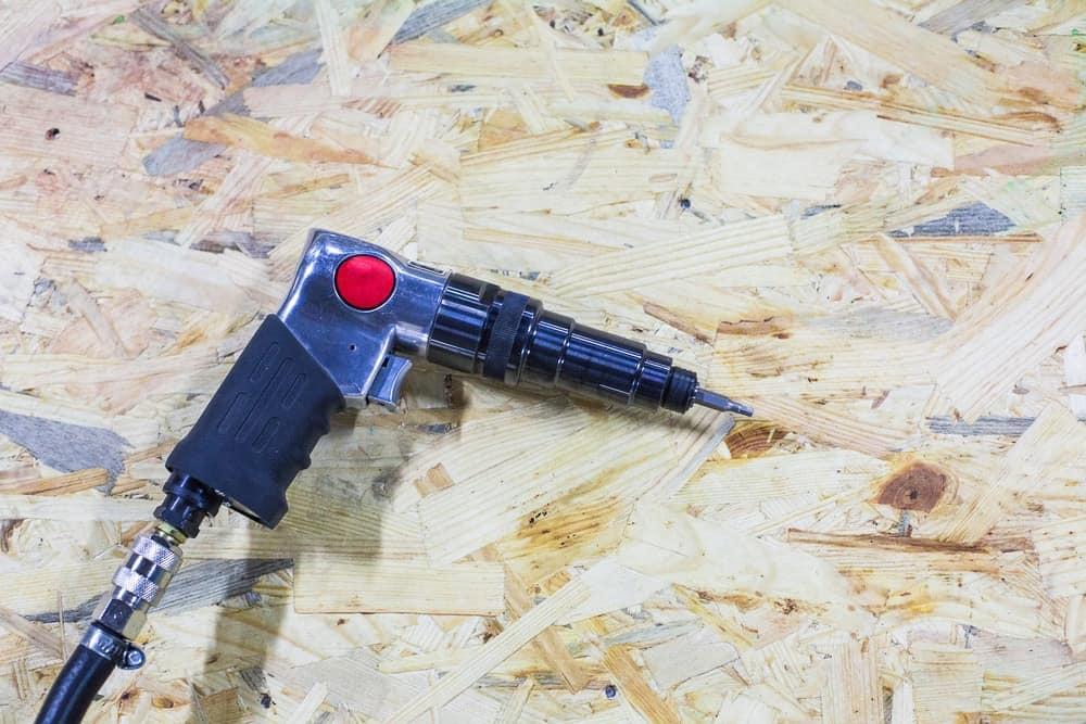 A pneumatic screwdriver with pistol grip.