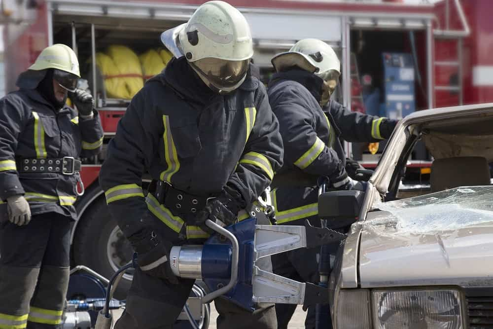 Firefighters are at work as they try to open a car using pneumatic shears.