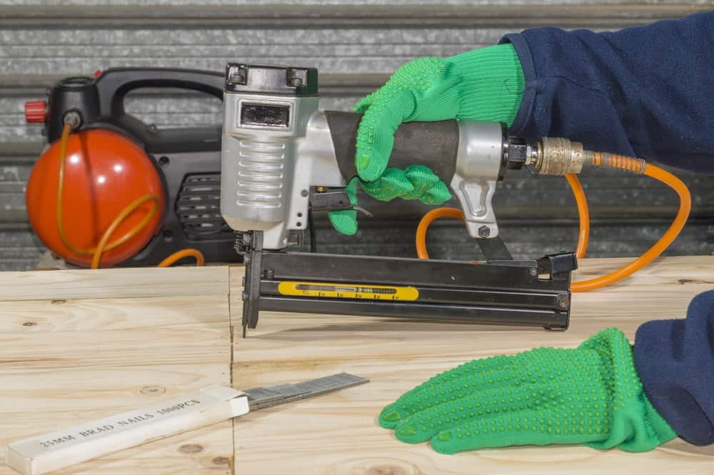 The pneumatic staple gun is being used to join board panels.
