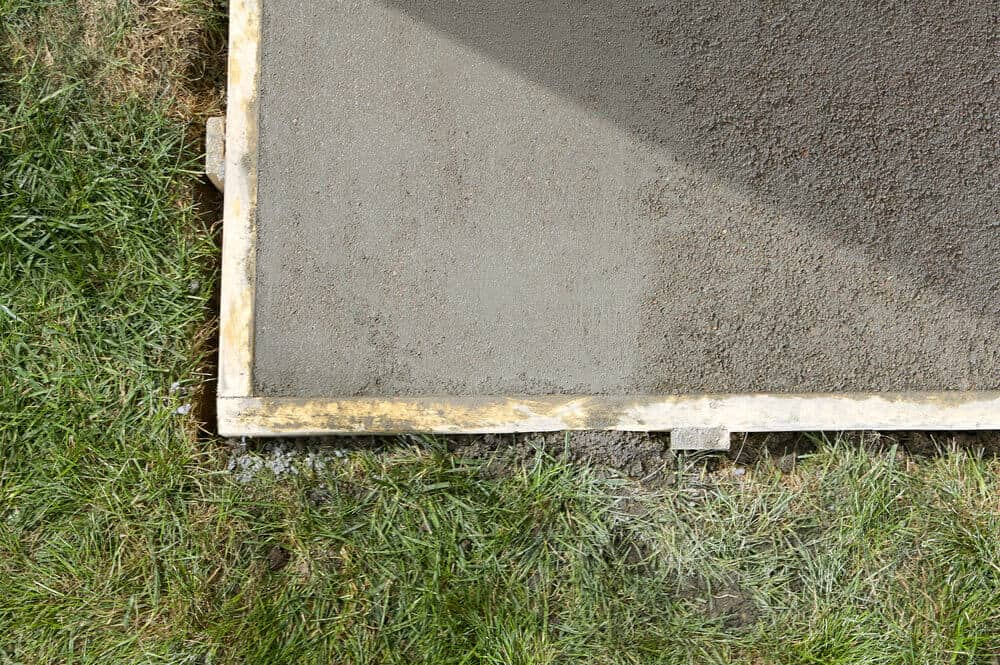 Wet, poured concrete that will serve as a lawn edging.