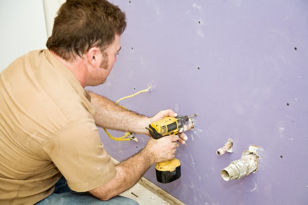 Man is using a yellow power drill to drill holes on the wall.