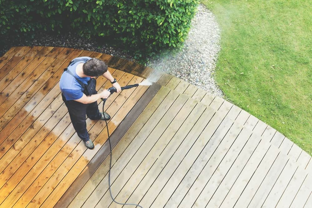 A man is using a pressure washer to remove dirt from the elevated wooden deck.