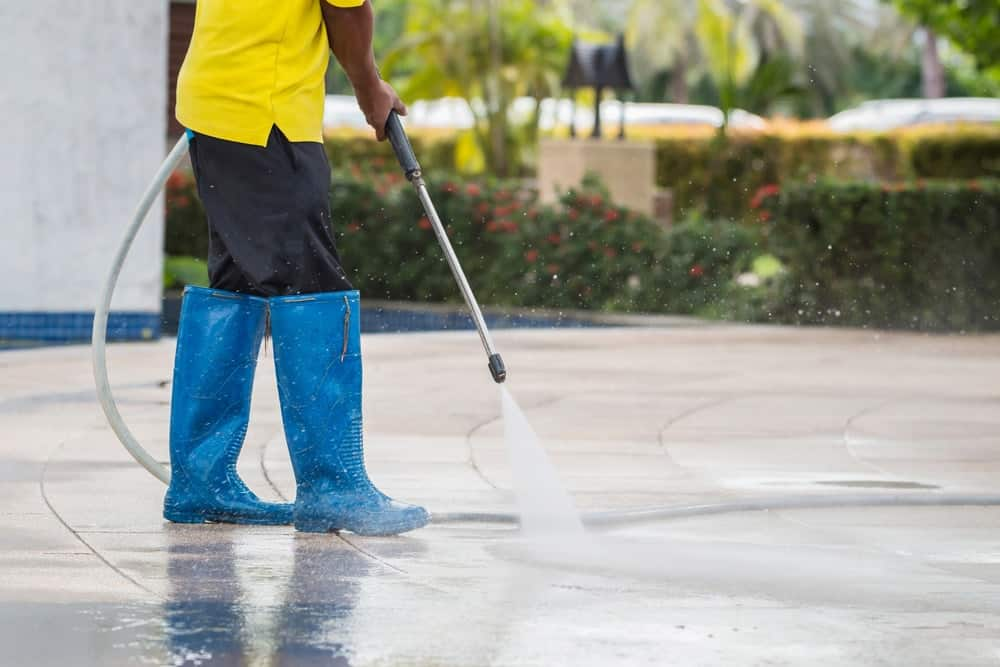The laborer is using a pressure washer to clean the concrete pavement.