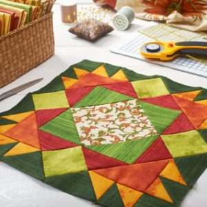 A set of quilting tools with a color fabric patchwork at the center.