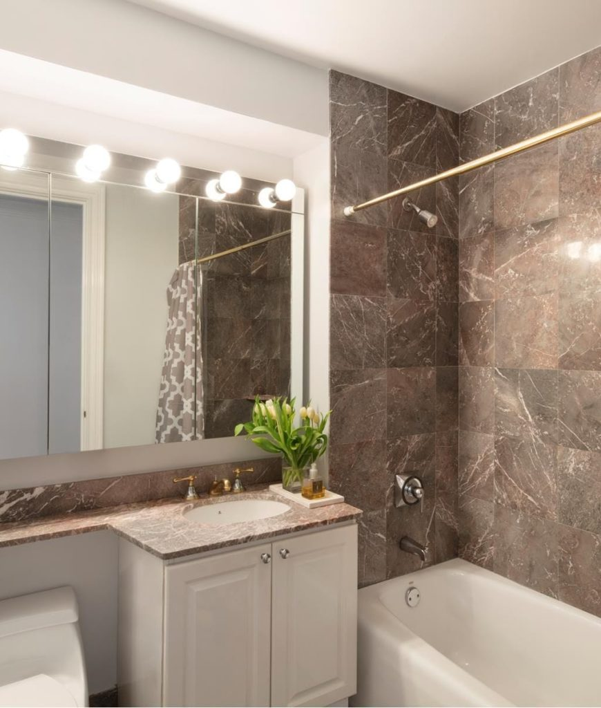 Another bathroom featuring a soaking tub with a curtain and a stylish tiles wall.