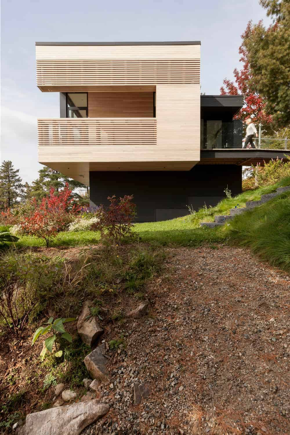 A large modern house with a wooden exterior and offers a nice balcony.