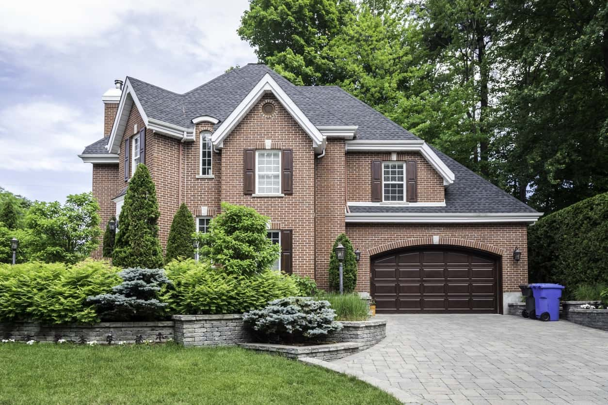 Luxurious suburban house with sloping roof, single garage, and brick driveway.