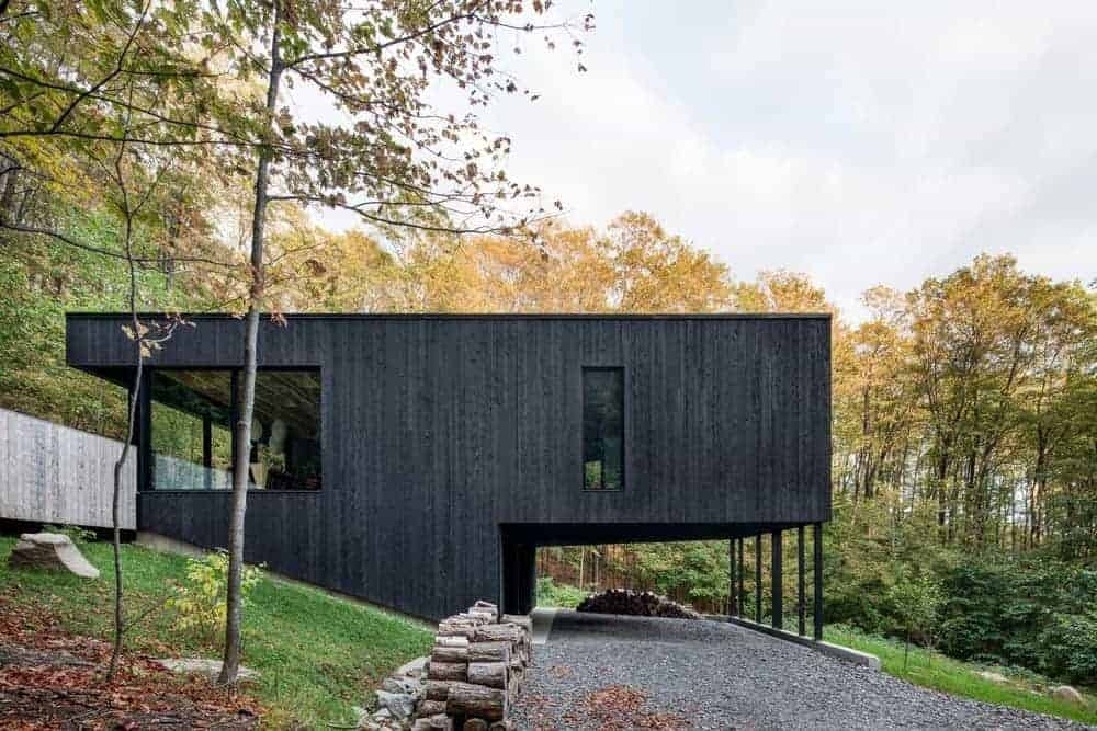 A modern customized home with a wooden exterior painted in black.