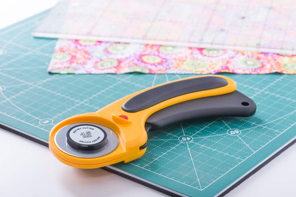 The rotary cutter is on top of a green cutting mat.