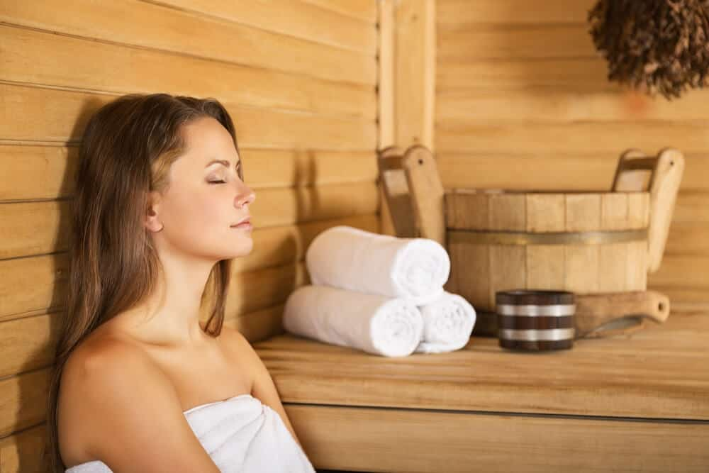 A woman relaxing and enjoying her rest time inside a a sauna room.