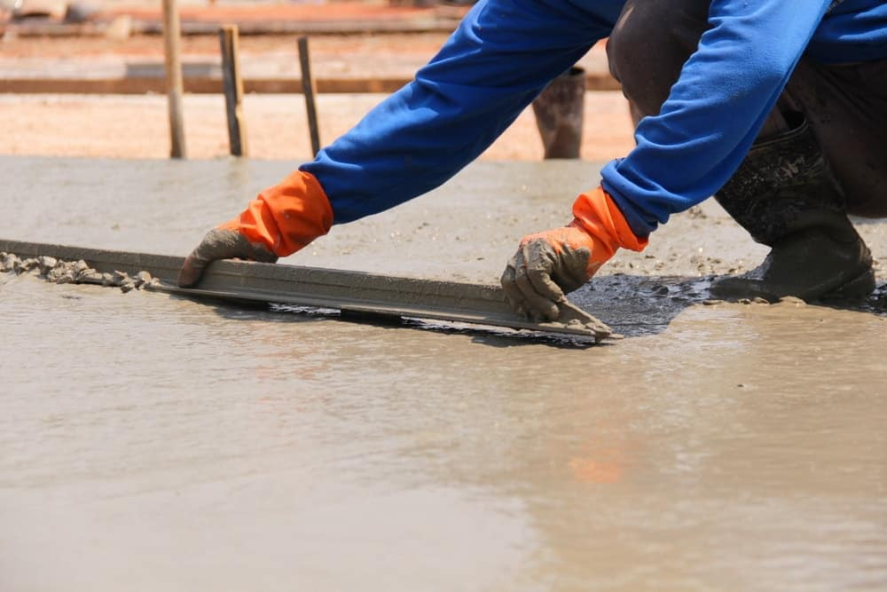 The screed is being used by the construction worker to even out the application of the cement.