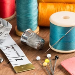 A typical sewing tool set consisting of pins, thimble, spools of thread, and measuring tape, among others.