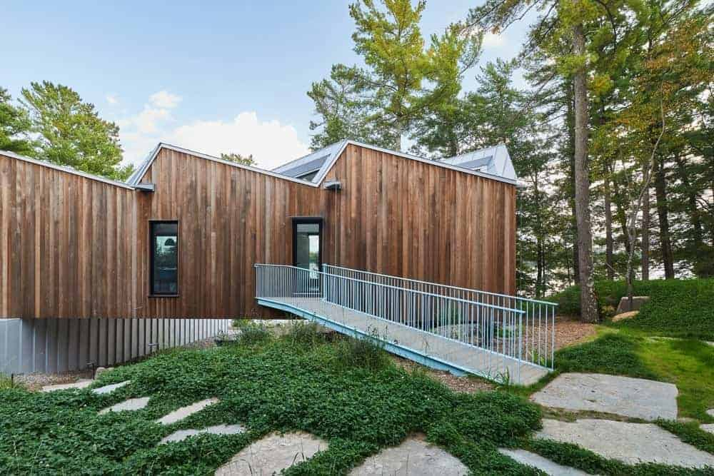 This house features a wooden exterior along with a gorgeous garden with a walkway.