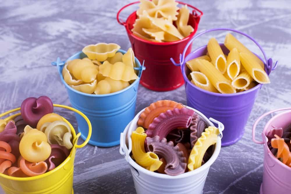 Small and colorful buckets with uncooked pasta inside.