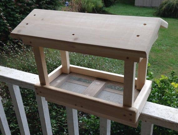 Mounted, nicely-roofed cedar bird feeder with a smooth finish.