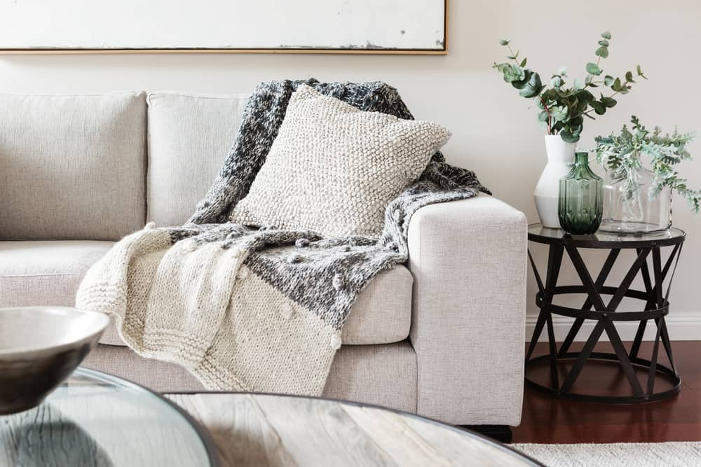 Off-white sofa with throw pillow and blanket in living room