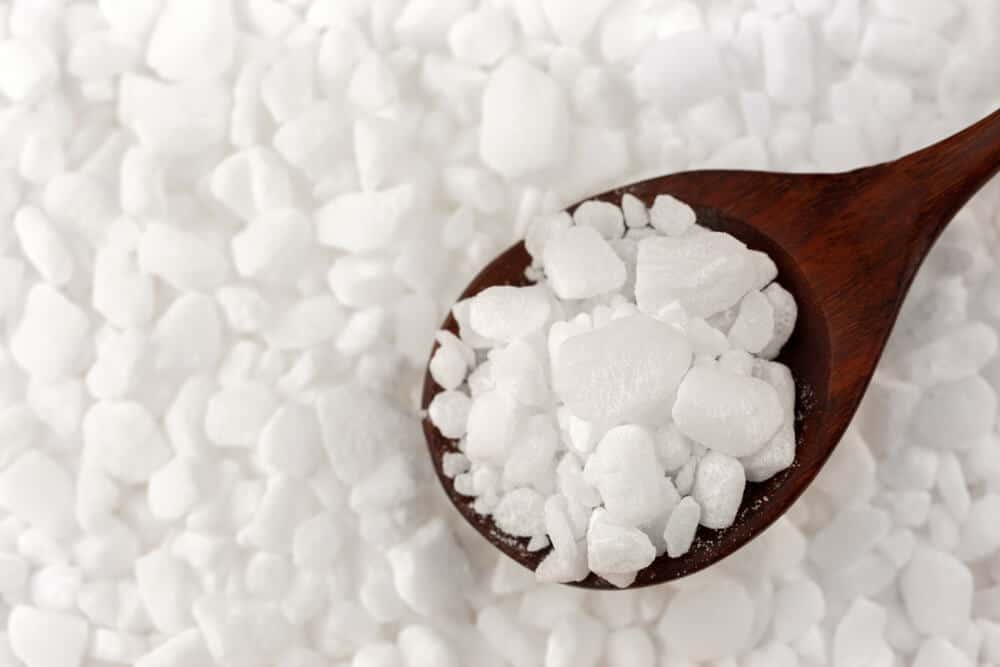 White chunks of softener crystals in a wooden spoon.
