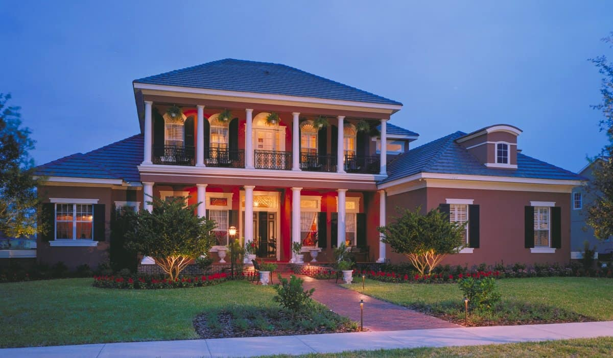 A southern colonial home with a stylish red exterior and beautiful lawn and garden area.