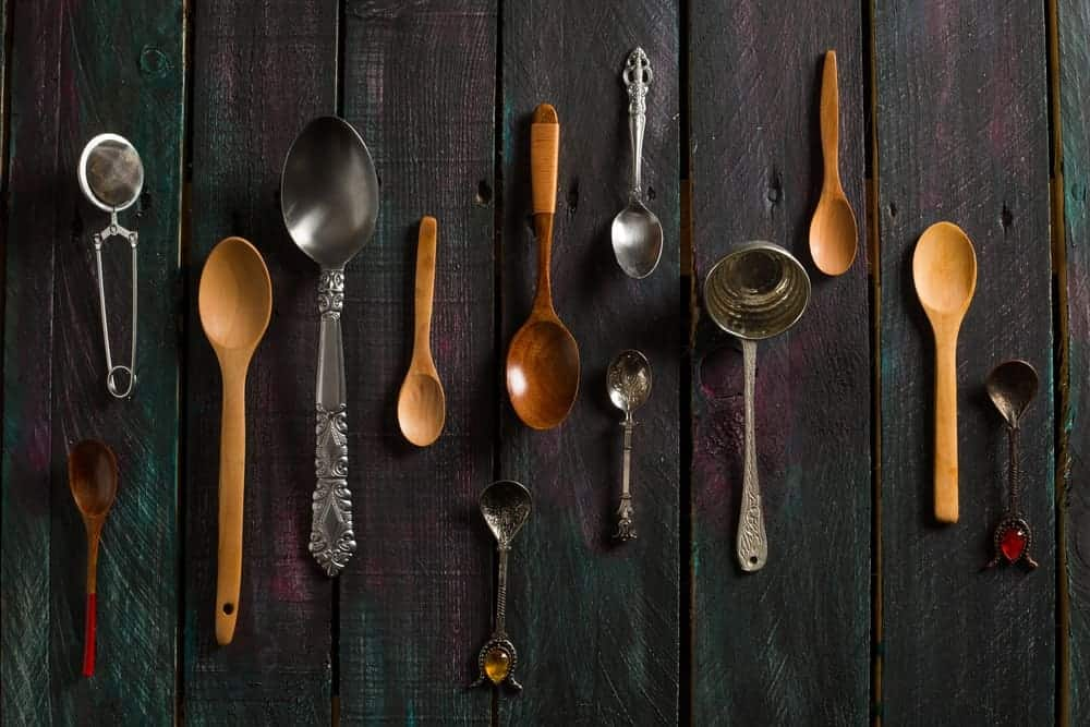 Different types of spoon laid on a rustic table.