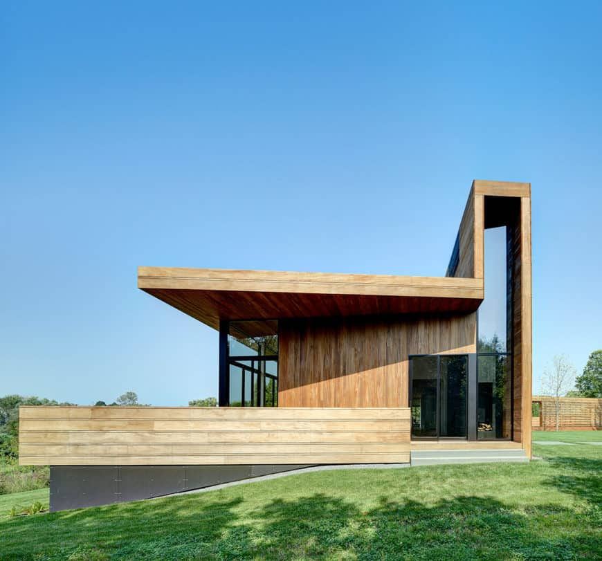 A large modern house with a wooden exterior along with a sprawling yard and lawn area.