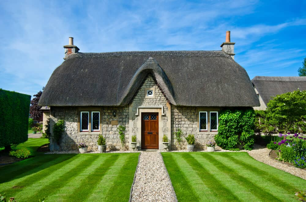 This stone house is something you will see in the urban areas. It is a bungalow-type of home with a brown wooden door and french windows. Its maintained lawn goes well with its stoned walkway.