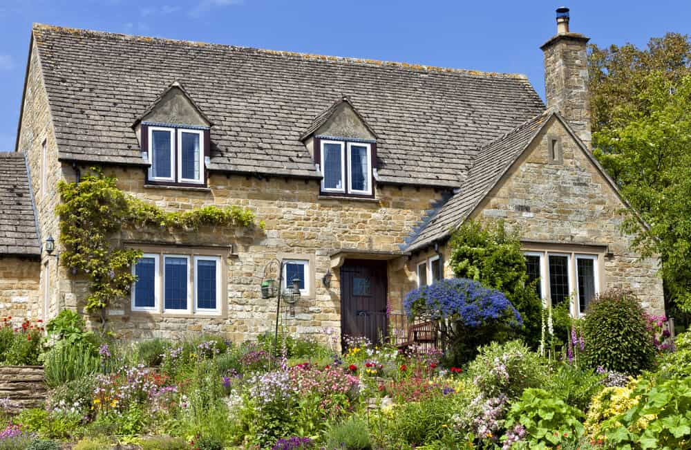 A simple, neutral-toned stone house with a garden full of colorful flowers.