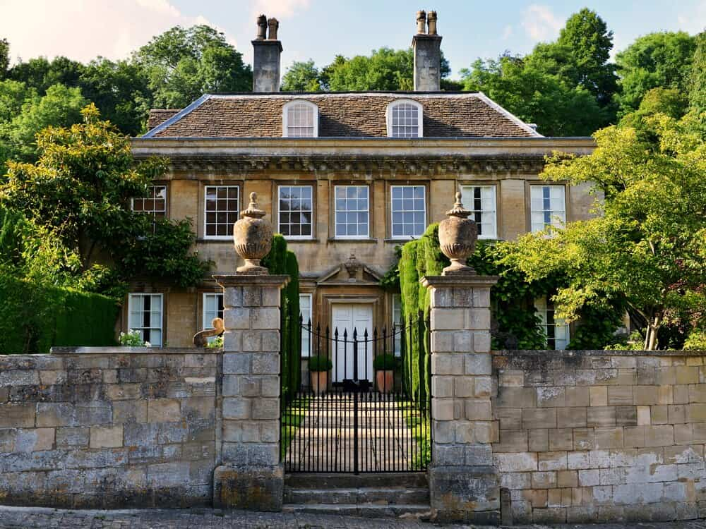 A large stone house with two chimneys and lots of windows. What makes this house extravagant is its stone fences with a metal gate, very regal.