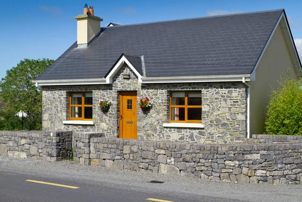 A small, one-floor stone house with a wooden door and window frames, surrounded by a stone fencing. The wood accents of this sturdy house complement well with its stone exterior.