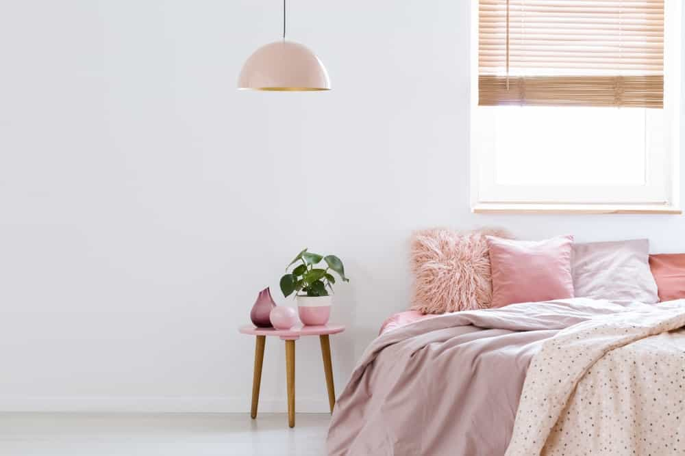 Feminine white bedroom with pink bed, pendant lighting, and stool as nightstand alternative.
