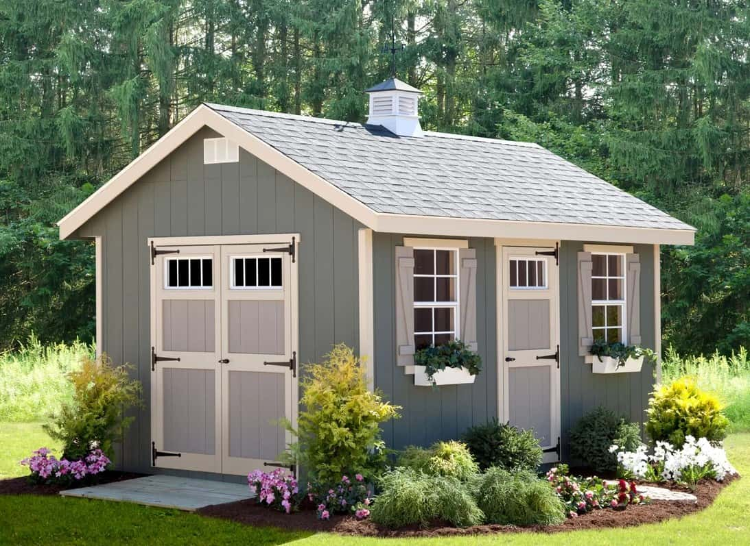 Gray storage shed surrounded by beautiful plants and flowers.