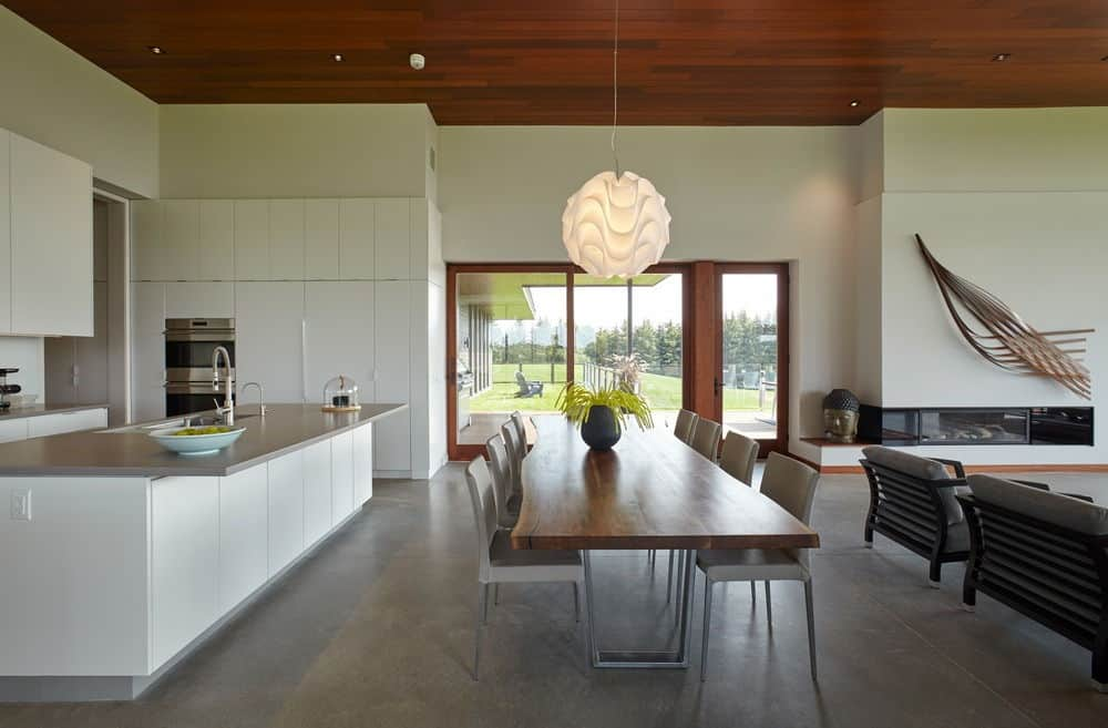The home's dining and kitchen looks beautiful with its modish look along with a nice pendant light. Photo credit: Maciek Linowski
