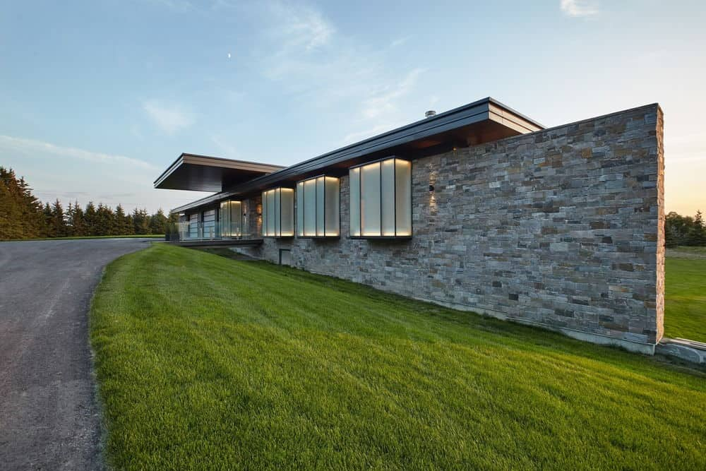 Outdoor side view of the house from the driveway featuring the beautiful lawn. Photo credit: Maciek Linowski
