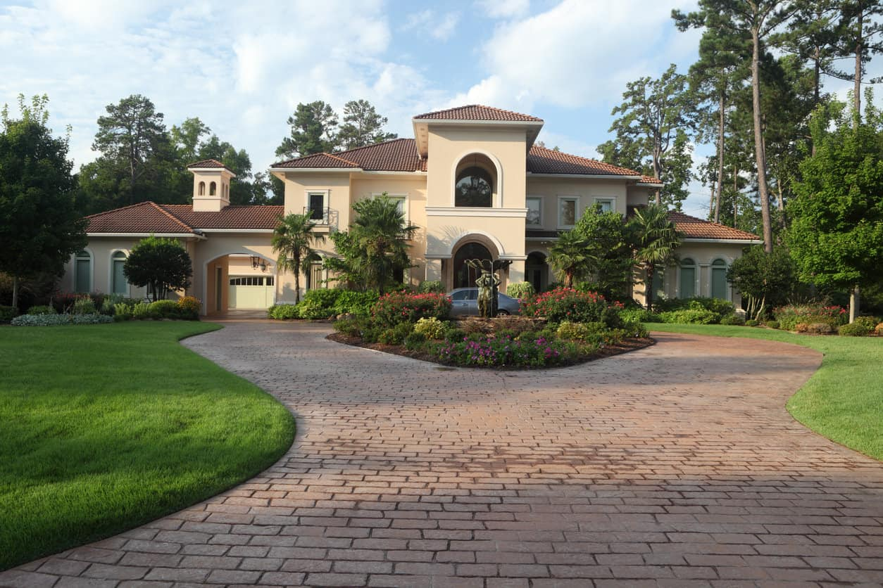 Luxury home exterior under early morning light. Sedan in driveway.