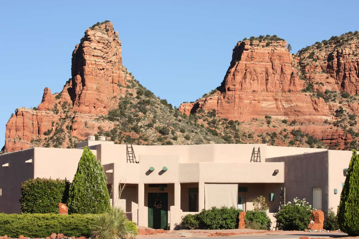 Santa Fe styled desert Southwest mansion with eroded red rock buttes in the background. Yavapai County, Arizona, 2013.