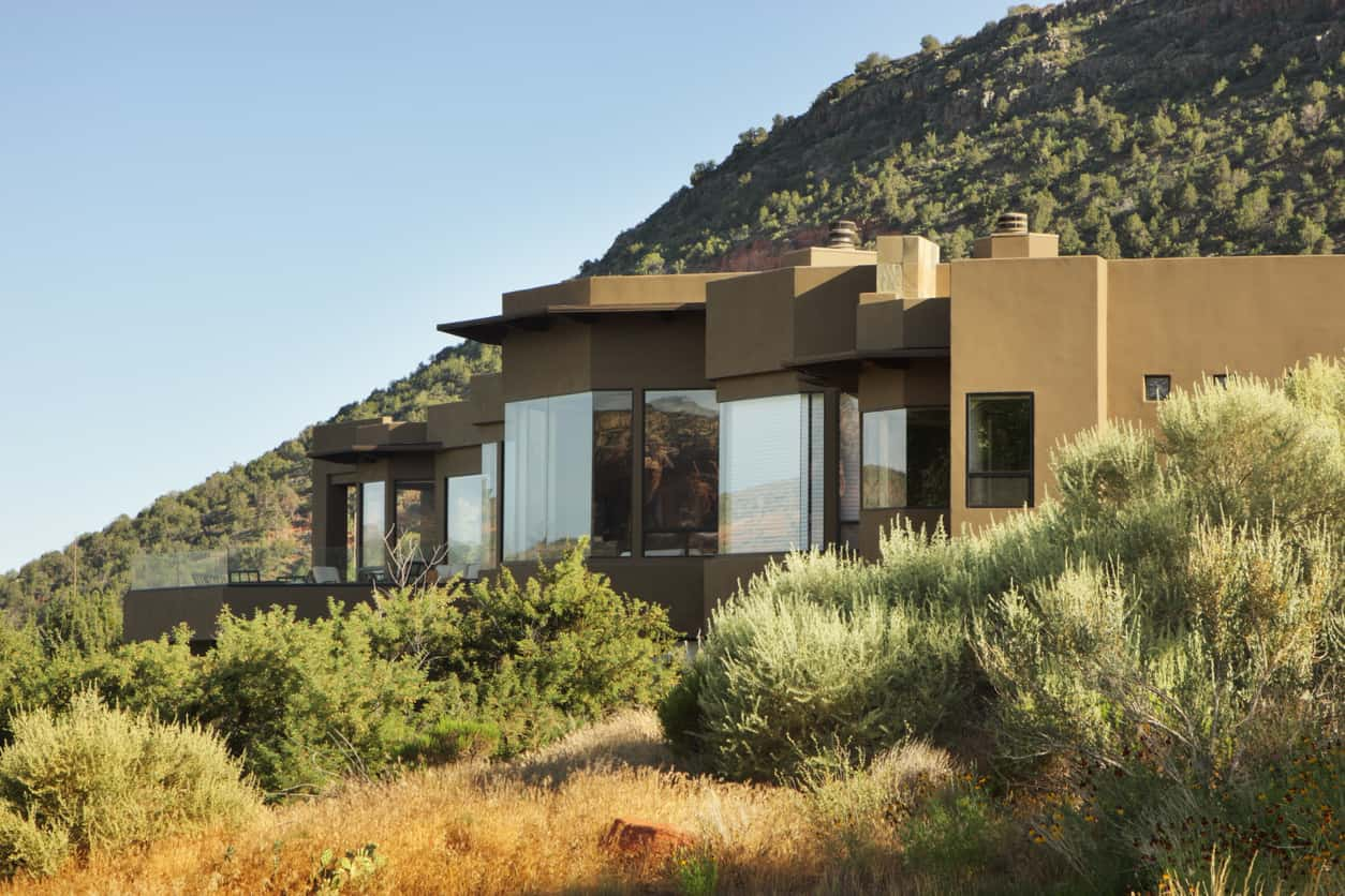 Stucco luxury house with glazed windows at the foot of a hill surrounded by desert plants.