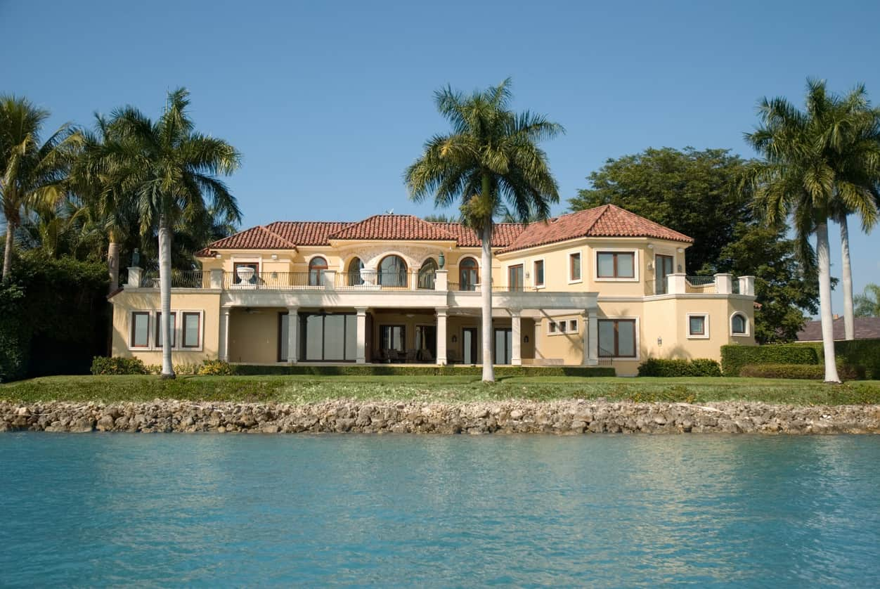 A large waterfront house with boxed hedges and palm trees.