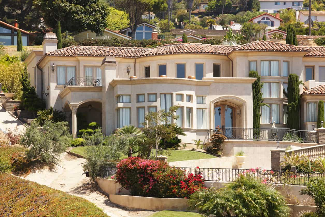 A Mediterranean-styled stucco and tiled roof home facade.