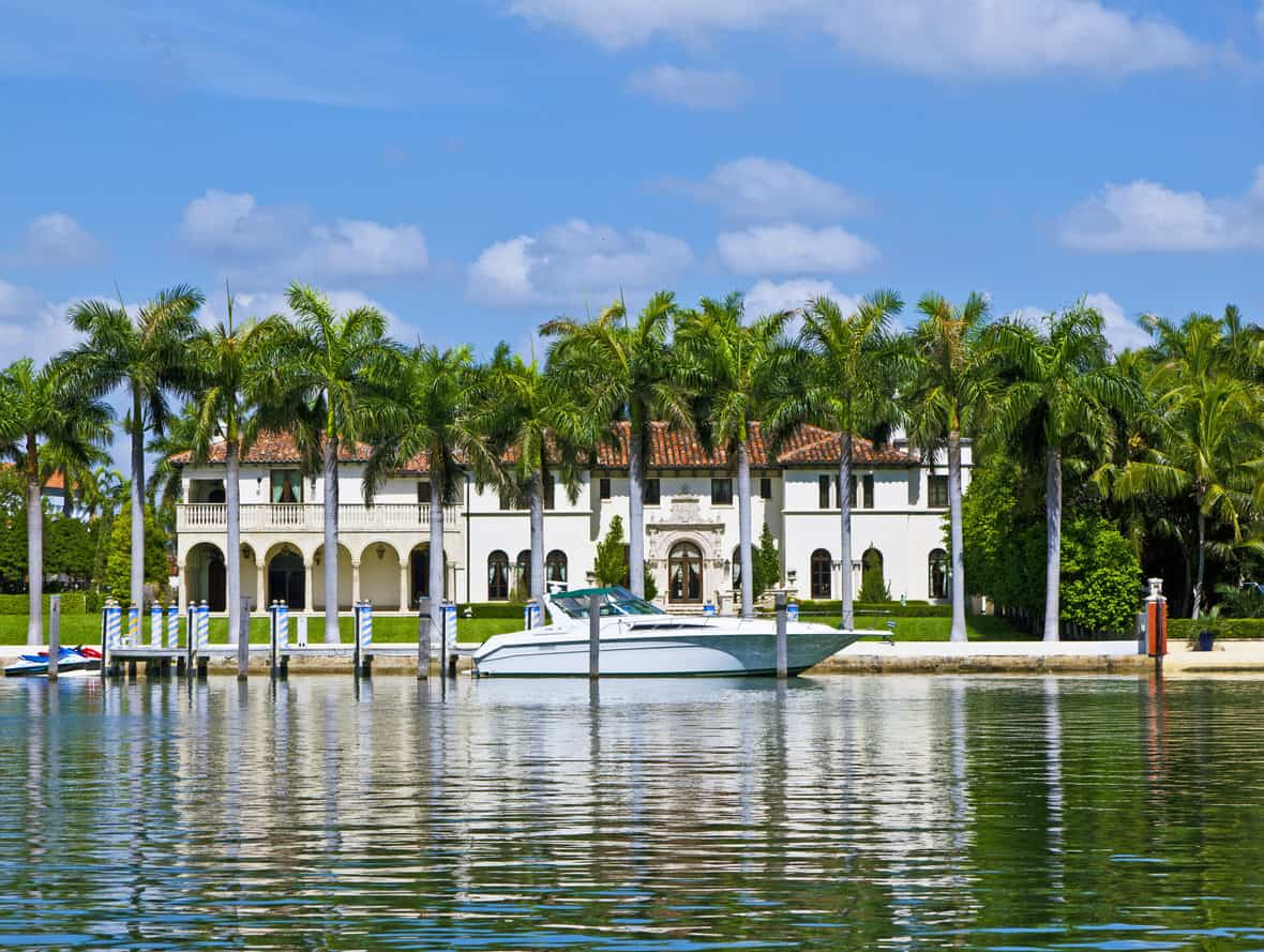 A row of palm trees stand in front of the luxury waterfront house and a yacht docked at the harbor.