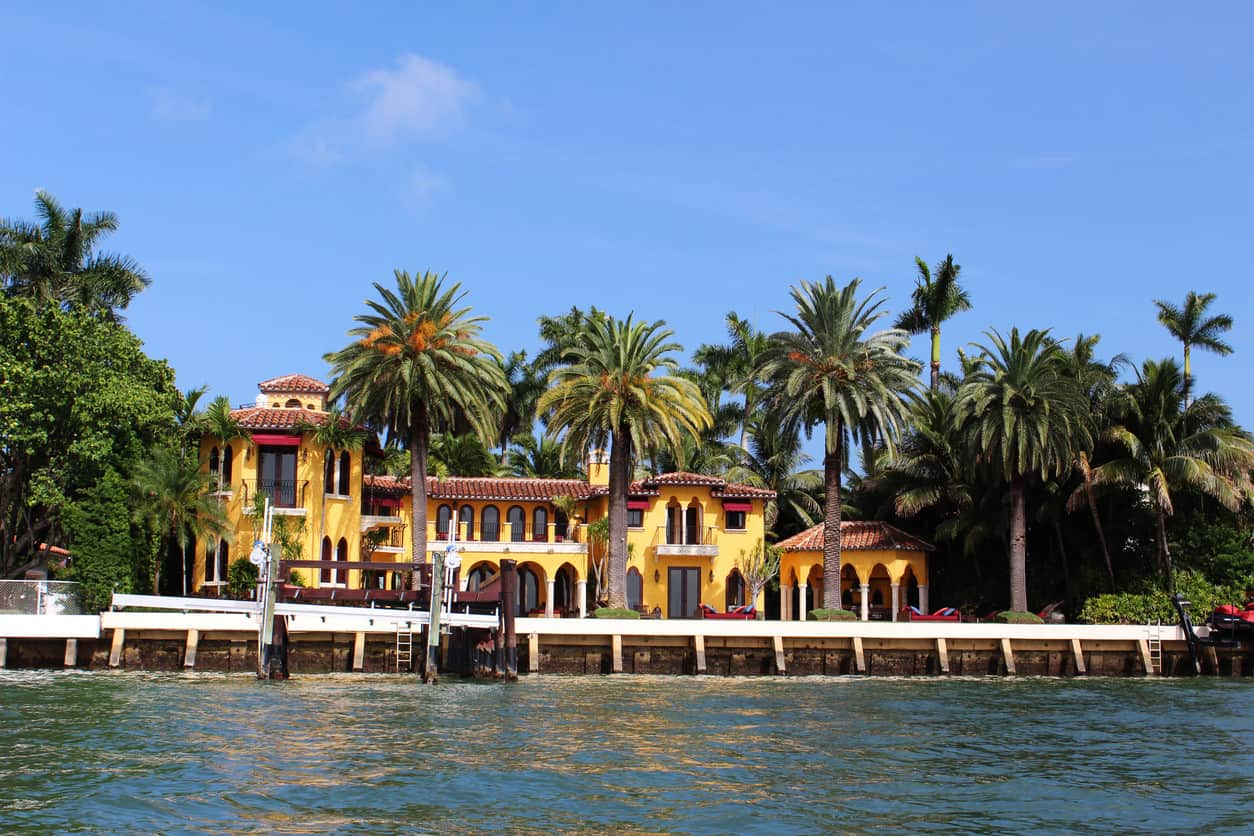 Bright yellow luxury waterfront house surrounded by palm trees under a clear blue sky.