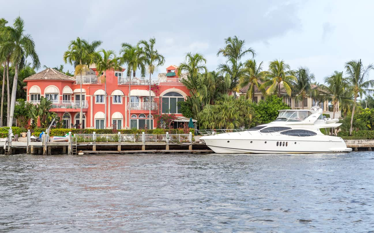 Large luxury waterfront house surrounded by palm trees and a yacht docked by the harbor.